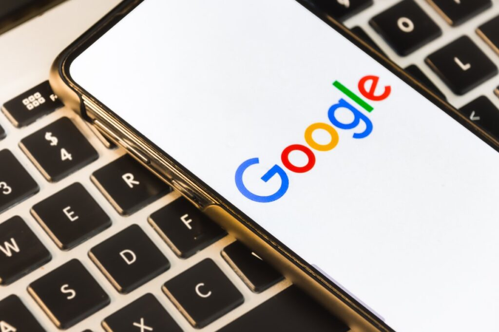A mobile phone with a white screen showing the Google logo, on top of a keyboard